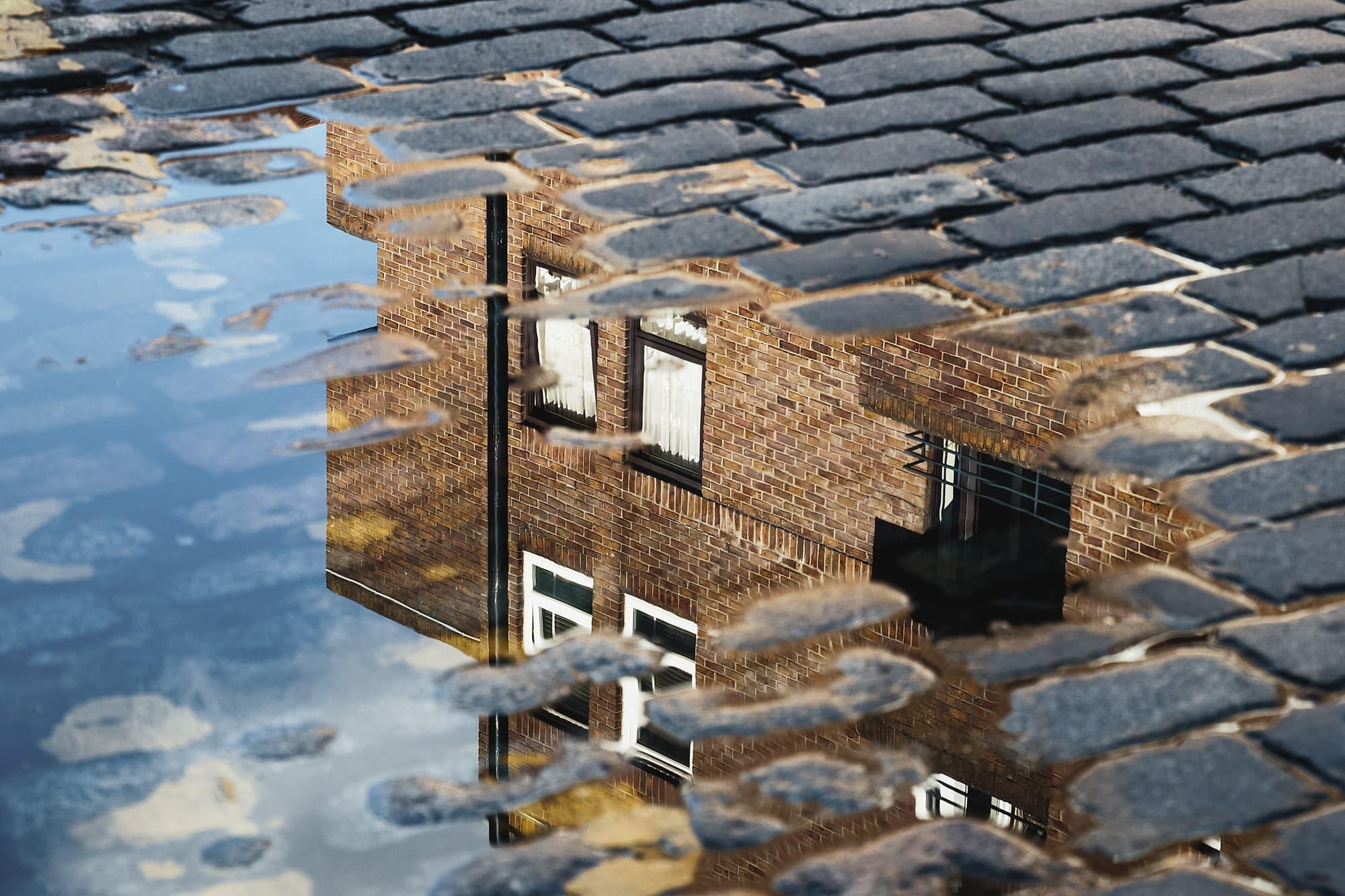 cobblestone-reflection-house-puddle-after-rain